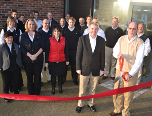 Jerry Moye [right], Cobb president, cuts the ribbon at the opening of the new offices, with Roy Mutimer general manager for Cobb Europe and staff