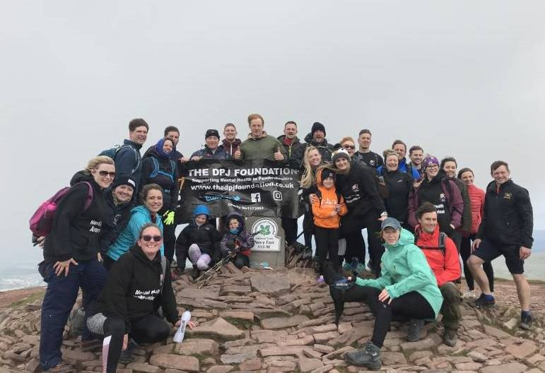 Matt Launder, Dan Launder, George Collins and Gareth Owen pictured with friends, family and supporters after completing the 9 Peaks Challenge