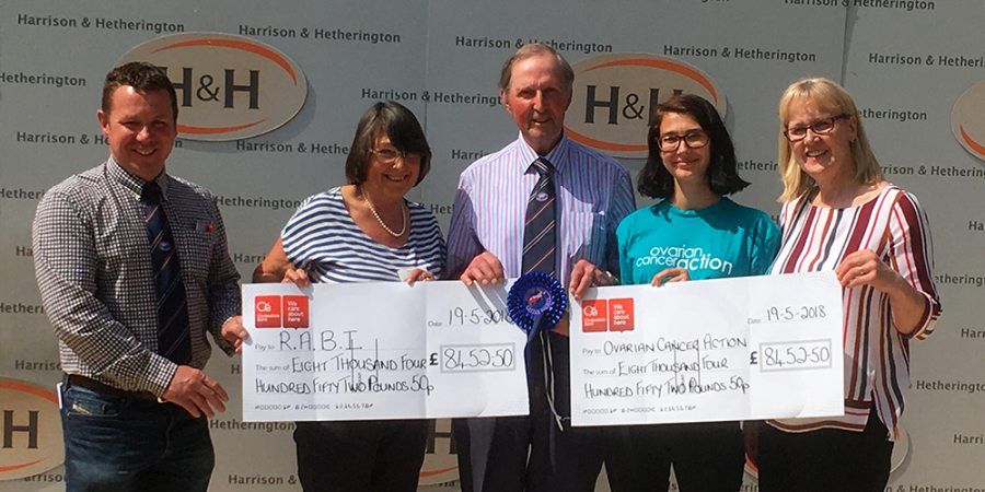 Emyr (centre) presenting cheques to representatives of his two chosen charities following a cattle sale in 2018